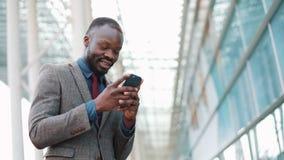 Молодой африканец Americanman используя app на smartphone в городе около бизнесмена центра офиса красивого молодого используя сток-видео