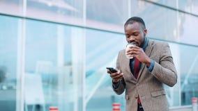 Молодой африканец Americanman используя app на smartphone в городе около бизнесмена центра офиса красивого молодого используя видеоматериал