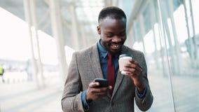 Молодой африканец Americanman используя app на smartphone в городе около бизнесмена центра офиса красивого молодого используя акции видеоматериалы