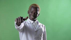 Молодой африканский белокурый доктор показывая большие пальцы руки-вверх и усмехаясь на человеке камеры, счастливых и успешных в  акции видеоматериалы