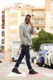 Молодой африканский бизнесмен идя и говоря на сотовом телефоне в городе Стоковое Изображение RF