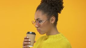 Молодой африканский студент выпивая горячую чашку напитка и смотря грустно в камеру видеоматериал
