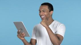 Молодой африканский человек возбужденный для успеха пока используя планшет, голубую предпосылку