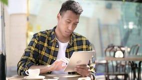 Молодой африканский человек используя планшет, на открытом воздухе кафе акции видеоматериалы
