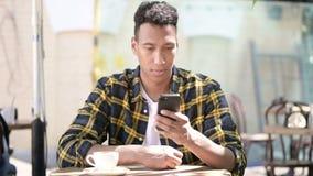 Молодой африканский человек используя смартфон, на открытом воздухе кафе сток-видео
