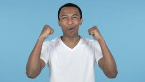 Молодой африканский человек празднуя успех, голубую предпосылку