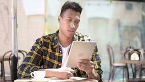 Молодой африканский человек реагируя к отказу на планшете, на открытом воздухе кафе видеоматериал