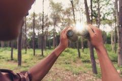 Молодой африканский человек смотря через бинокулярное в лесе, Trave Стоковые Изображения RF