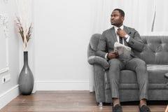 Молодой Афро-американский бизнесмен в сером костюме читая газету пока сидящ на софе стоковая фотография