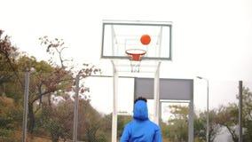 Молодой Афро-американский играя баскетбол на улице и бросать шарик к корзине неудачно Slowmotion видеоматериал