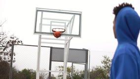 Молодой Афро-американский играя баскетбол на улице и бросать шарик к корзине успешно Slowmotion съемка акции видеоматериалы