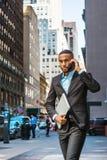 Молодой Афро-американский путешествовать бизнесмена, работая в новом Yor Стоковые Изображения