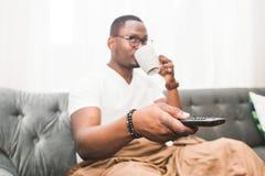 Молодой Афро-американский человек, покрытый с одеялом, смотря ТВ дома стоковые фото