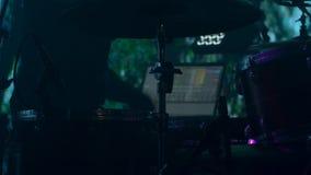 Молодой барабанщик в ярких светах на этапе играя ритм сток-видео
