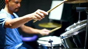 Молодой барабанщик играет на барабанах, руки играют на барабанах в музыкальном зале, музыкальные инструменты и развлекательную ко акции видеоматериалы