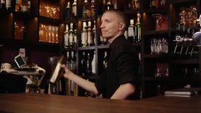 Молодой бармен в коктеиле интерьера бара тряся и смешивая спирта Профессиональный портрет бармена на работе в ночном клубе акции видеоматериалы