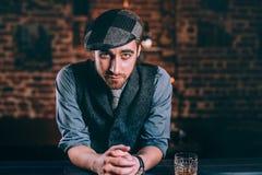 Молодой бармен наслаждаясь ночой в баре, имеющ алкогольные напитки на счетчике Стоковые Фотографии RF