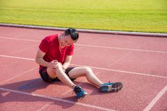 Молодой бегун имея боль на колене между бежать стоковые фото