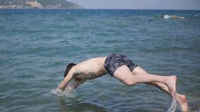 Молодой без рубашки атлетический человек скача в воду берегом океана стоковые фото