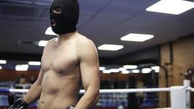 Молодой без рубашки боксер в черном положении маски похитителя на боксерском ринге дыша глубоко для того чтобы утихомирить его не видеоматериал