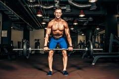 Молодой без рубашки человек делая тренировку deadlift на спортзале Стоковые Изображения