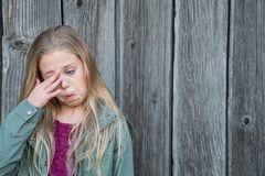 Молодой белокурый глаз затирания девушки стоковые фото