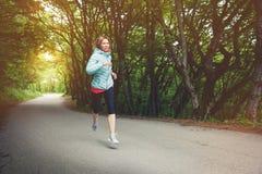 Молодой белокурый ход женщины практикует outdoors в парке горы города в лучах леса теплых через стоковое фото rf