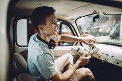 Молодой белокурый человек паркует его автомобиль ventage стоковые фото