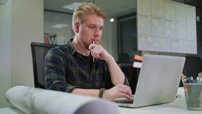 Молодой белокурый человек работая на компьтер-книжке внутри помещения акции видеоматериалы