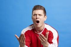 Молодой белый мужской вентилятор спорт поддерживая его команду стоковое фото