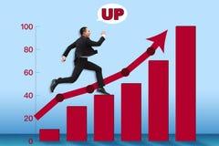 Молодой бизнесмен бежать к верхней части диаграммы стоковое изображение