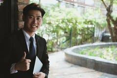 Молодой бизнесмен в костюме держа цифровую таблетку пока стоящ Стоковые Изображения