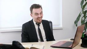 Молодой бизнесмен в костюме сидя в офисе и ручки говорят с насмешкой вне, делают смешными сторонами 60 fps сток-видео