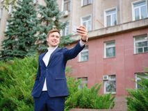 Молодой бизнесмен в костюме outdoors с телефоном в руках Стоковое Изображение RF