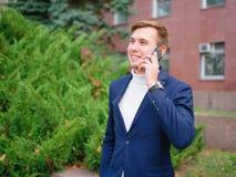 Молодой бизнесмен в костюме outdoors с телефоном в руках Стоковая Фотография