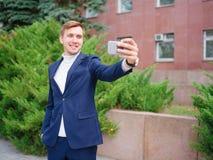 Молодой бизнесмен в костюме outdoors с телефоном в руках Стоковое фото RF