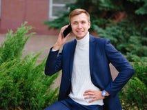 Молодой бизнесмен в костюме outdoors с телефоном в руках Стоковые Изображения RF