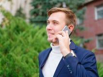 Молодой бизнесмен в костюме outdoors с телефоном в руках Стоковые Фотографии RF