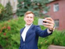 Молодой бизнесмен в костюме outdoors с телефоном в руках Стоковое Изображение