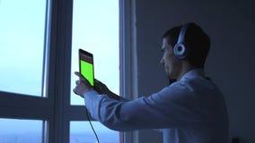 Молодой бизнесмен в наушниках использует планшет окном в вечере 3840x2160 видеоматериал
