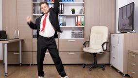 Молодой бизнесмен в официально костюме в офисе танцует и скачет arround сток-видео