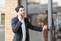Молодой бизнесмен говорит на телефоне и раскрывает дверь здания стоковые фотографии rf