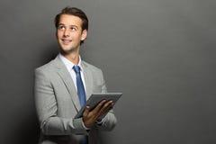 Молодой бизнесмен думая пока держащ таблетку стоковое фото rf