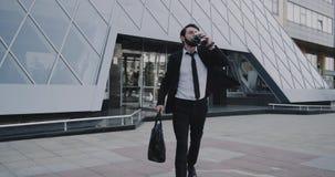 Молодой бизнесмен закончил его день работы приходит вне от современного здания держа кофе и портфель акции видеоматериалы