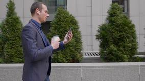 Молодой бизнесмен идет с беспроводными наушниками в его ушах и беседами на видео- разговоре на смартфоне