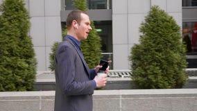 Молодой бизнесмен идет с беспроводными наушниками и агрессивно водит обсуждение на телефонном звонке