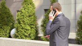 Молодой бизнесмен идя вниз по улице и агрессивно водит обсуждение на телефонном звонке