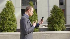Молодой бизнесмен идя вниз по улице и агрессивно водит обсуждение на видео- звонке