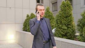 Молодой бизнесмен идя вниз по улице и беседы над телефонным звонком