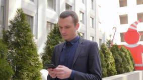 Молодой бизнесмен идя вниз по улице и написать сообщение на смартфоне